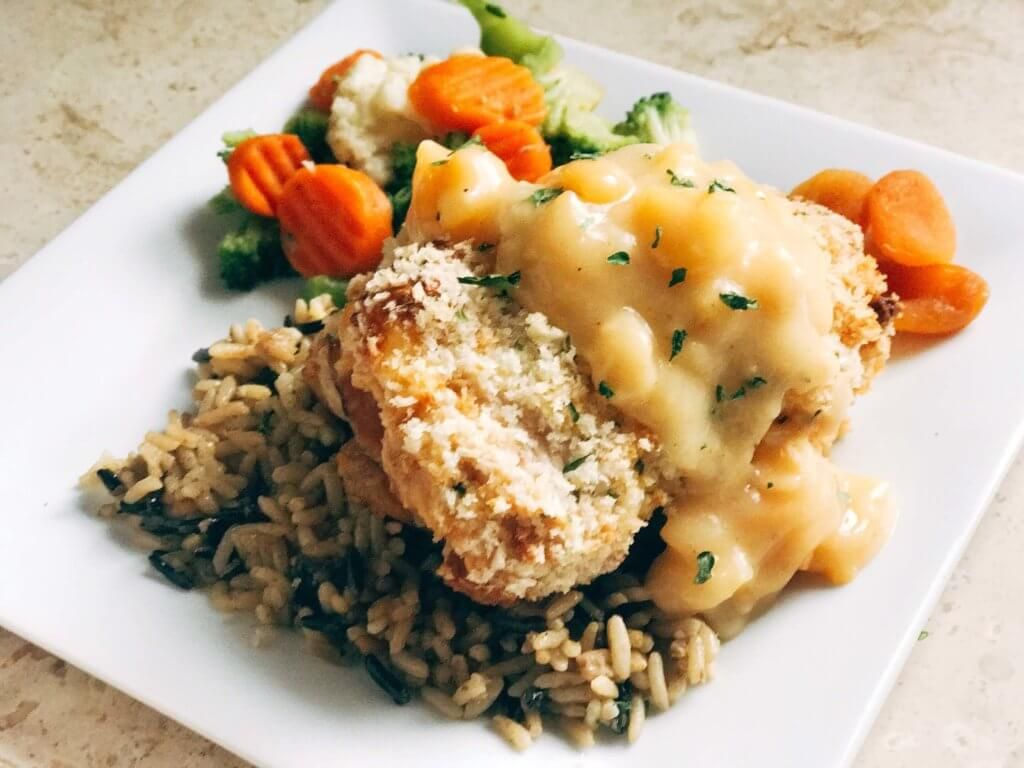 A slightly sweet twist on the classic! Dried apricots pair perfectly with the ham, monterey jack cheese, and seasonings in this recipe revamp. The creamy apricot white wine sauce is the perfect addition! A fun and memorable dinner that the entire family will love. Apricot Chicken Cordon Bleu | Three Olives Branch | www.threeolivesbranch.com