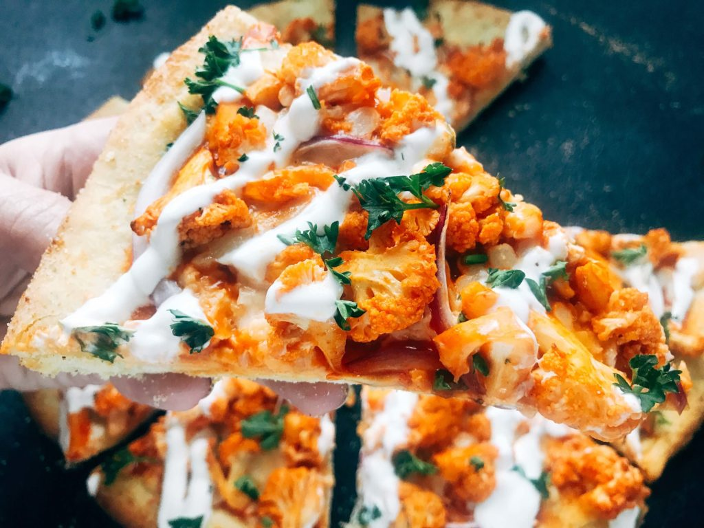 A vegetarian pizza recipe using the flavors of buffalo wings for inspiration. Roasted cauliflower is tossed with buffalo wing sauce on a ranch pizza crust. Great for game day and the Super Bowl to get a vegetarian buffalo recipe! Vegetarian Buffalo Cauliflower Pizza | Three Olives Branch | www.threeolivesbranch.com #superbowl #gameday #vegetarian #buffalowing