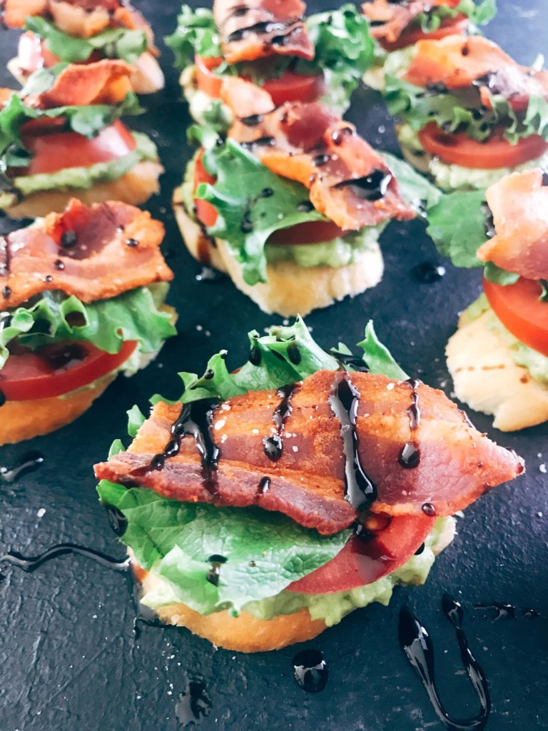 Quick and simple party appetizers. A twist on the BLT sandwich, these mini toasts are layered with avocado, tomato, lettuce, bacon, balsamic glaze, and some seasoned salt. Easy entertaining recipe. Avocado BLT Crostini | Three Olives Branch | www.threeolivesbranch.com #appetizer #blt #partyrecipe