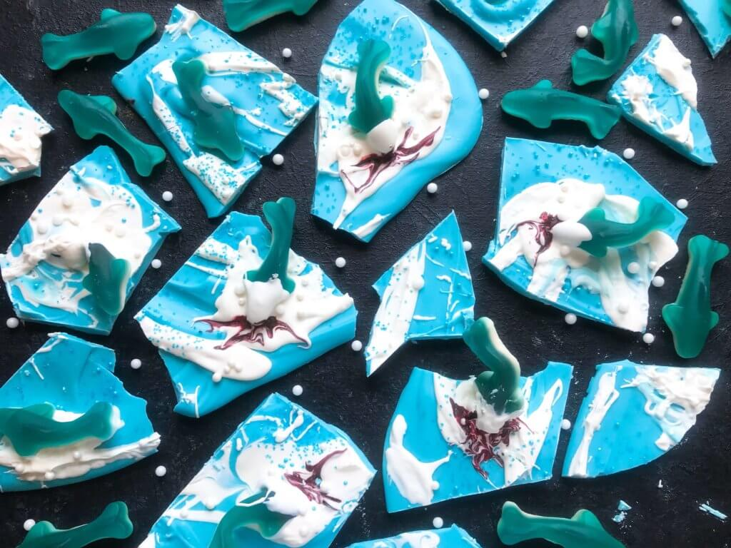 Just 10 minutes to make Shark Bark! Candy melts with sprinkles, gummy sharks, and a shark attack scene using red food gel. Gluten free (GF) quick and easy dessert recipe for shark or ocean party. Shark Week Shark Bark | Three Olives Branch | www.threeolivesbranch.com #sharkweek #ocean #sharkattack