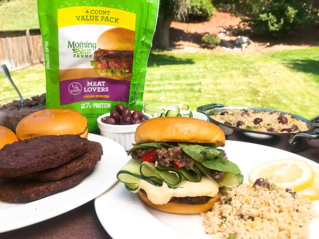Vegan burgers topped with cucumber, olive tapenade, roasted red peppers, hummus, and spinach. Made with MorningStar Farms® Meat Lovers Burgers, these burgers are ready in just 20 minutes. Vegan Mediterranean Burgers #grilling #MorningStarFarms #MakeRoomOnYourGrill #ad