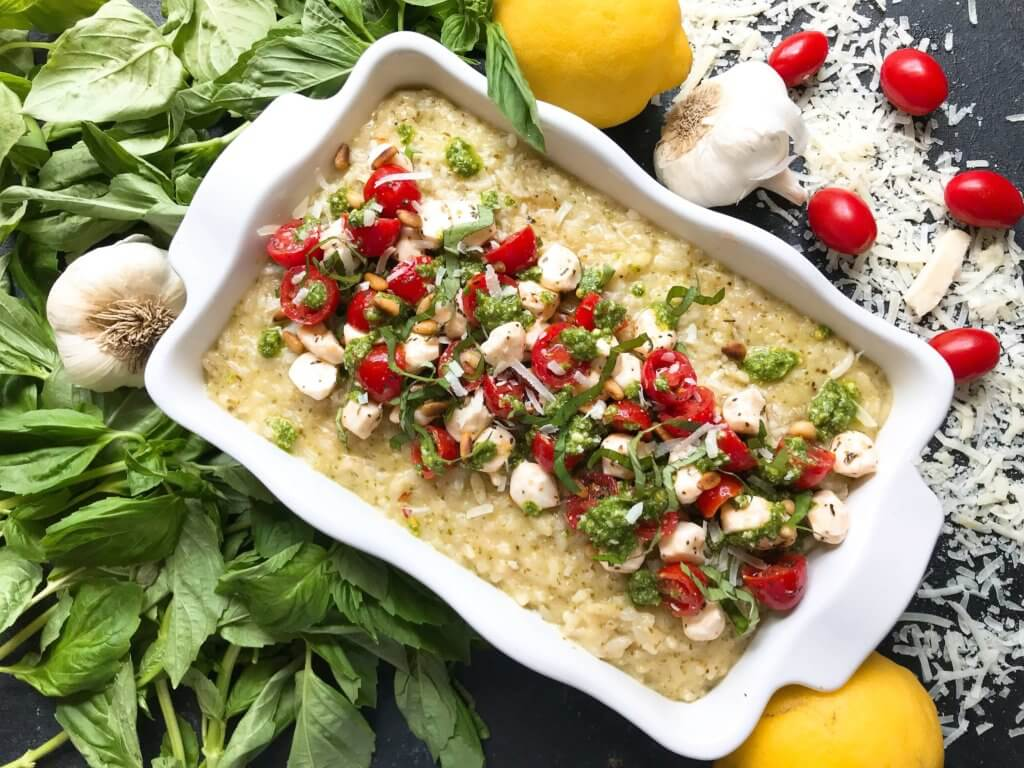 Fresh and bright flavors infused into an Italian risotto recipe. Fresh basil pesto, cherry tomatoes, and fresh mozzarella mixed into a creamy Parmesan cheese risotto. Gluten free and vegetarian comfort food. Add a protein like chicken, steak, beef, shrimp, tofu, or eat on its own. Caprese Pesto Risotto | Three Olives Branch | www.threeolivesbranch.com #italianrecipe #risotto #vegetarianrecipe