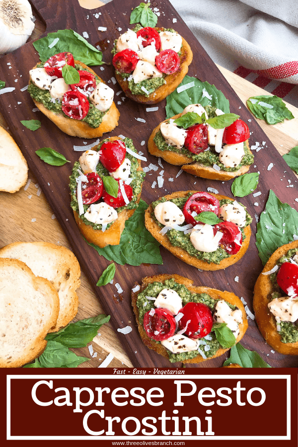 Pin image for Caprese Pesto Crostini on wood board with title at bottom