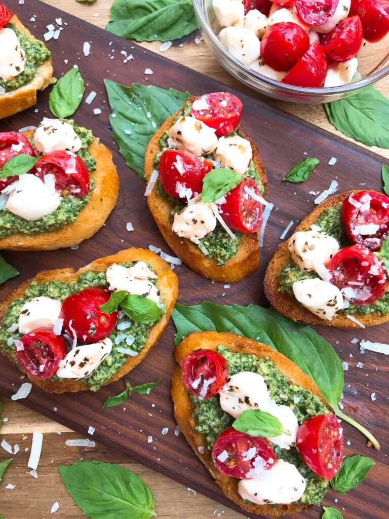 Caprese Pesto Crostini on a wood board