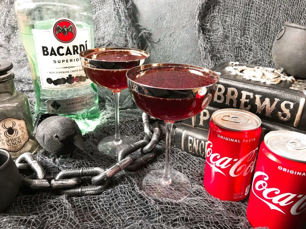 Halloween cocktails with decorations, a rum bottle, and Coke cans