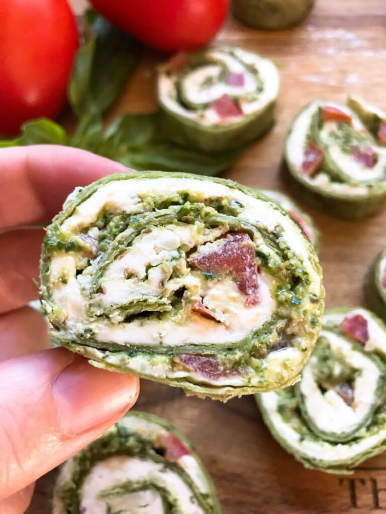 Fast and simple party appetizer recipe. Vegetarian Caprese Pesto Pinwheels Roll Ups are made of cream cheese, mozzarella, Parmesan, basil pesto, and tomatoes rolled in a flour tortilla. Easy finger food for entertaining or game day. #basilpesto #caprese #pinwheels #appetizers