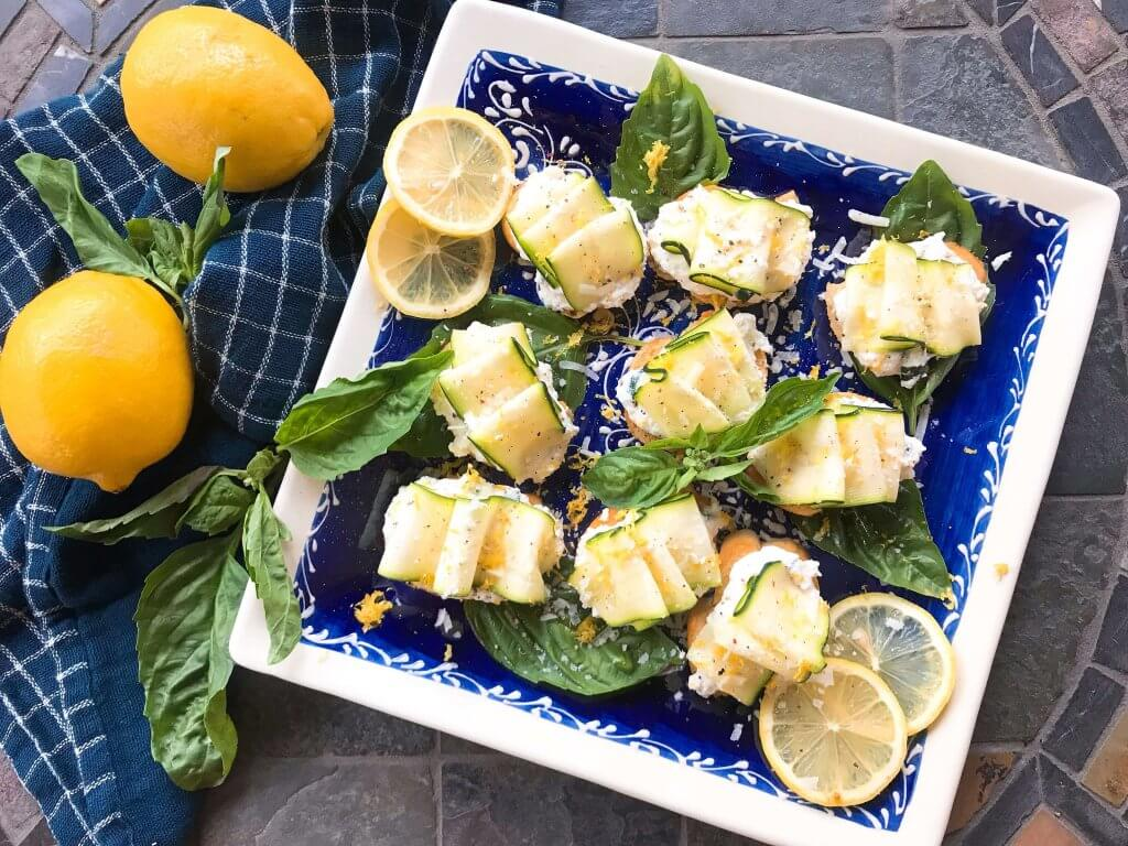 A blue plate with Zucchini Lemon Ricotta Crostini surrounded by lemons and basil