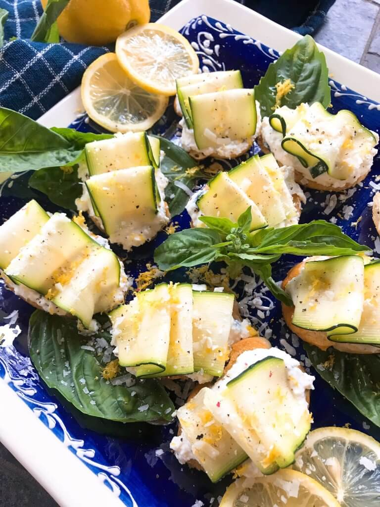 A close up of Zucchini Lemon Ricotta Crostini on a blue and white plate