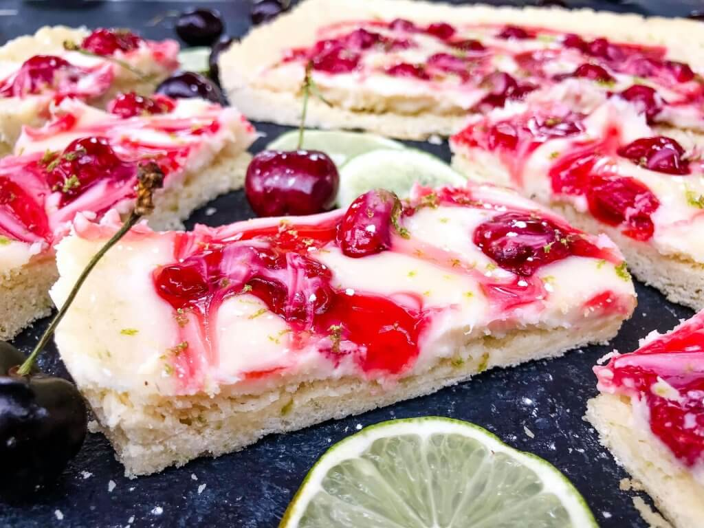 This fast and easy Cherry Limeade Tart is a perfect summer dessert recipe. A soft lime crust is filled with lime cream cheese filling and cherry pie swirls. #cherrylimeade #summerdessert #cherrydessert #tart