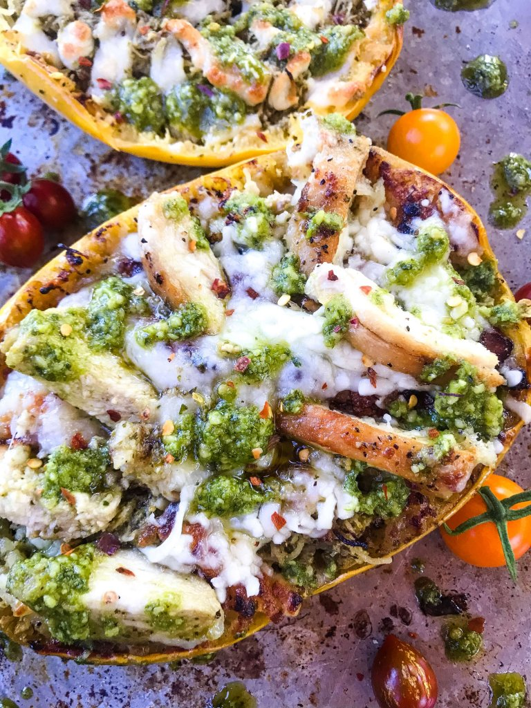 A half squash filled with chicken, pesto, and cheese