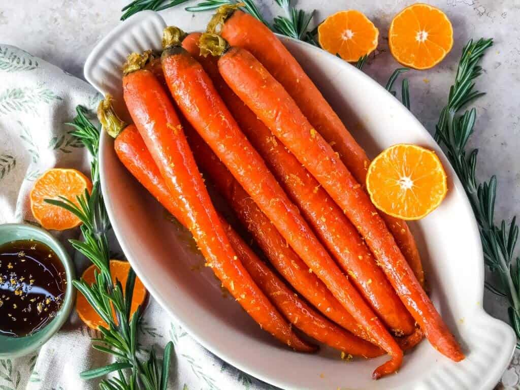Orange Maple Glazed Carrots are a fast and simple side dish recipe ready in 20 minutes! Perfect for holiday dinners like Easter. Fresh and sweet flavors of orange and maple syrup in a simple sauce. Gluten free and vegan. #glazedcarrots #easterrecipes #sidedishrecipes