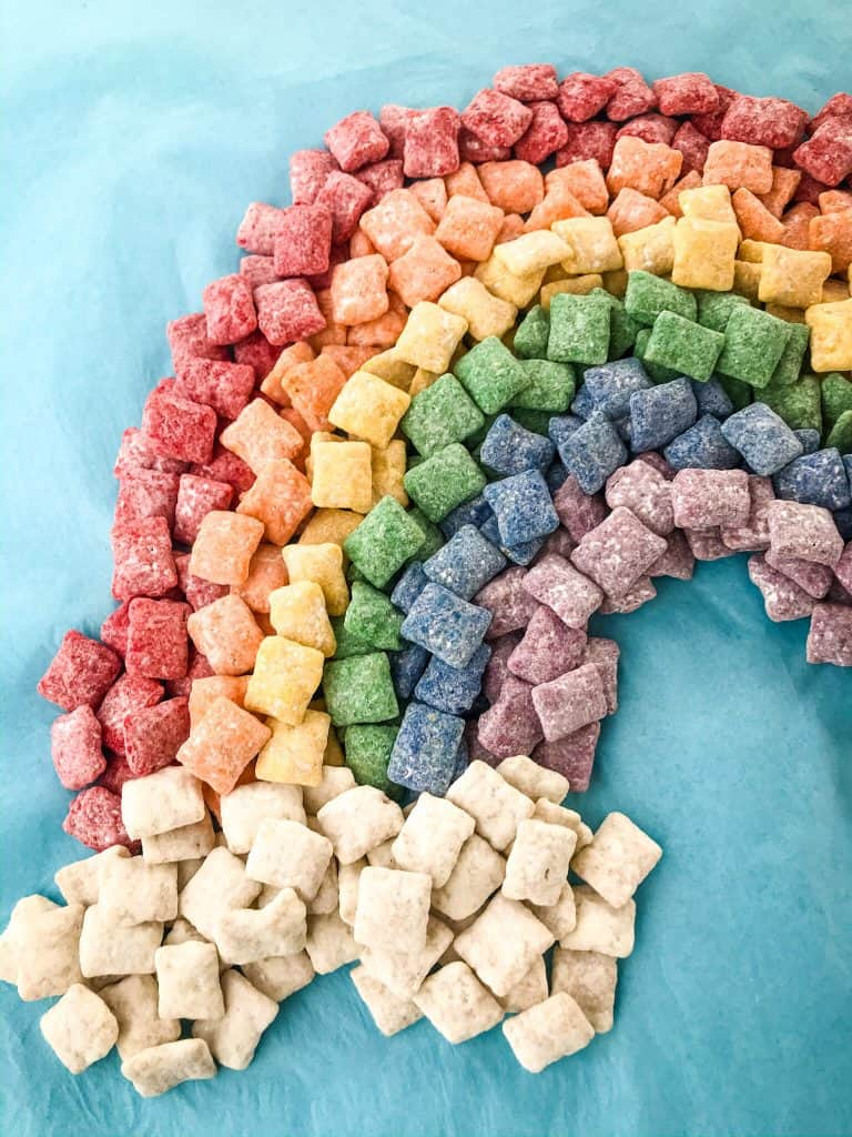 Rainbow Puppy Chow recipe is a colorful dessert perfect for a unicorn rainbow party, St Patrick's Day, or Pride month. Gluten free and vegetarian. #rainbowpuppychowrecipe #puppychow #rainbow #unicorn #pride