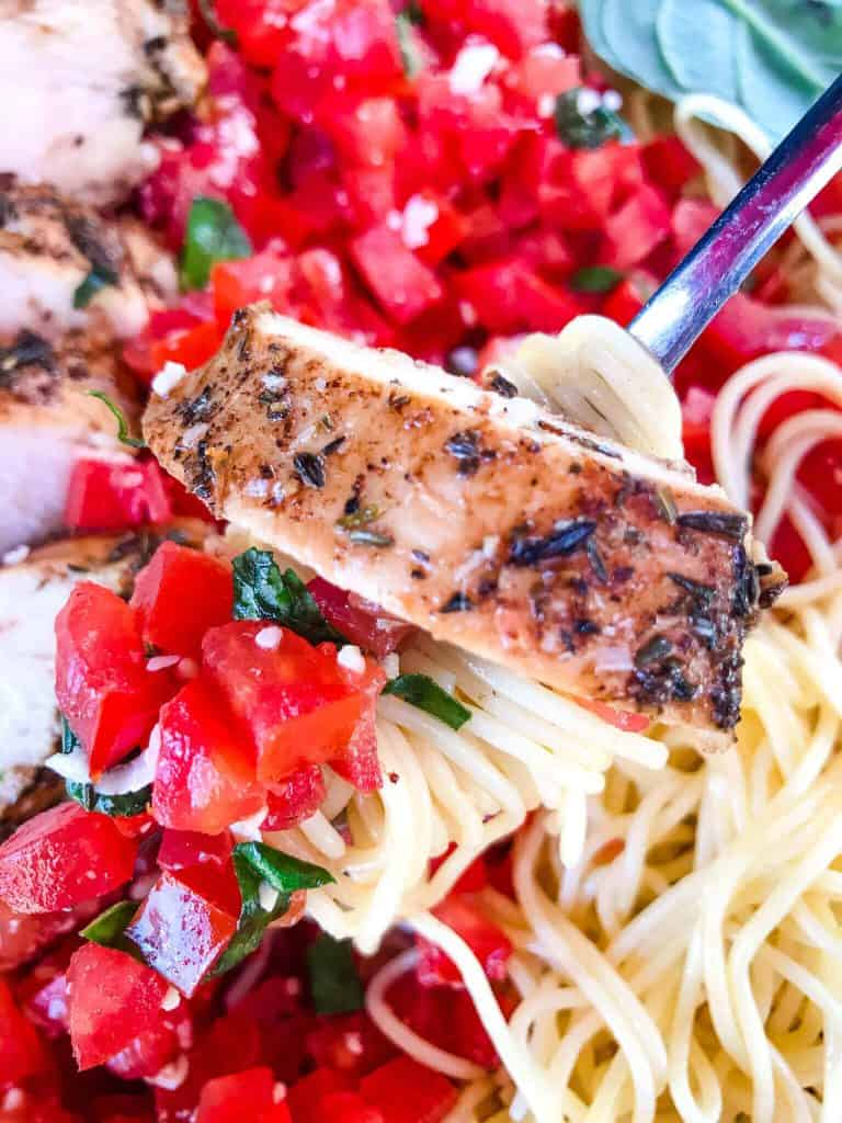 A fork scooping pasta with diced tomatoes and a slice of balsamic chicken