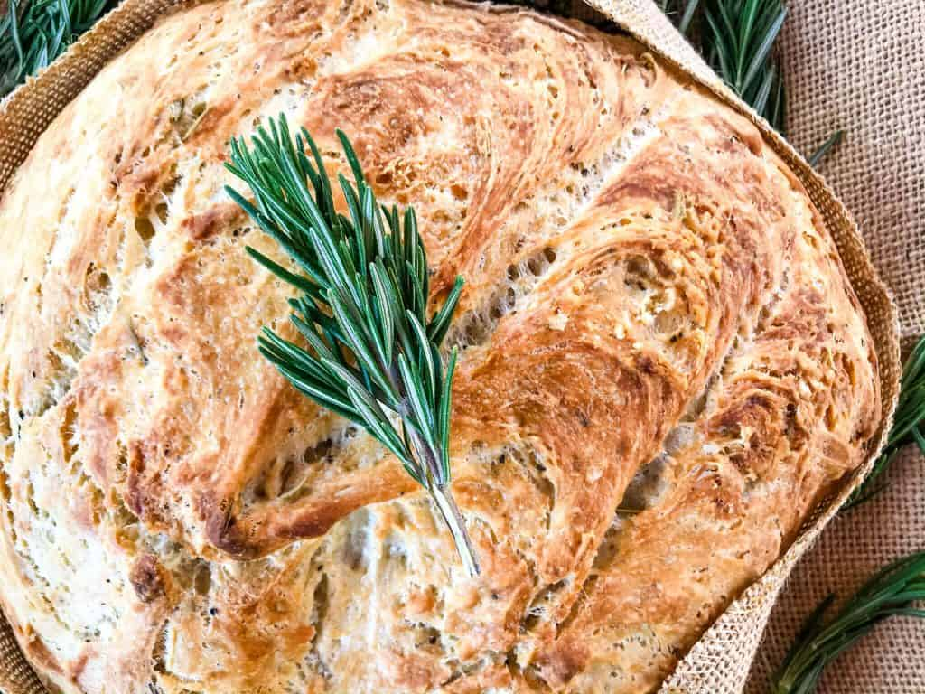 An easy homemade No Knead Rustic Rosemary Bread recipe. A dense, flavor filled bread loaf filled with rosemary oven baked in dutch oven. #nokneadbread #homemadebread #Italianbread