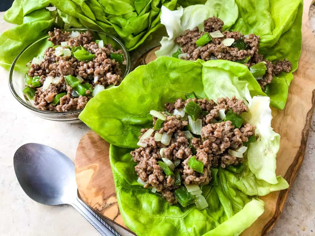 Philly Cheesesteak Lettuce Wraps are ready in less than 30 minutes! A healthy low carb, keto, gluten free recipe. Ground beef is mixed with bell pepper, onion, and provolone cheese for a simple beef lettuce cup. #phillycheesesteak #lettucewrap #groundbeef #healthyrecipe
