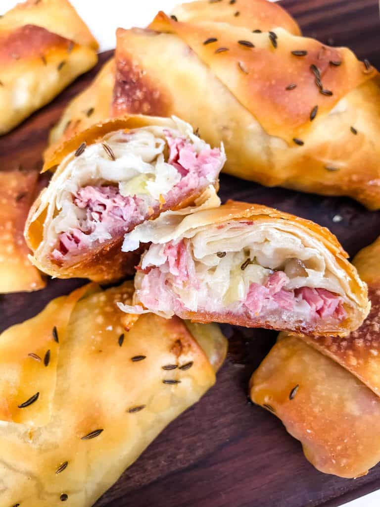 The inside of a corn beef egg roll on a pile of other egg rolls
