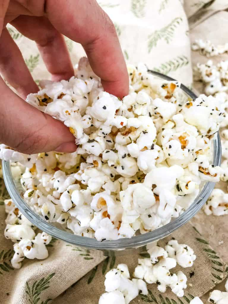A hand grabbing popcorn out of a bowl