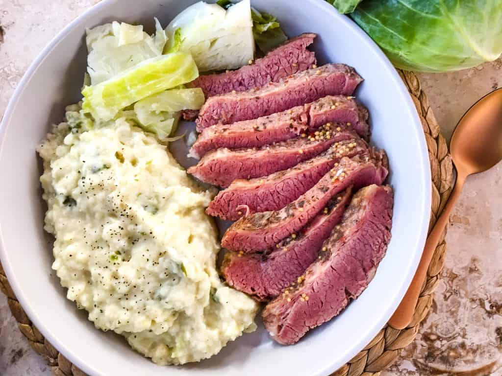 A dish of sliced corned beef with colcannon cabbage mashed potatoes and cabbage slices.