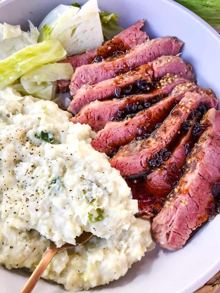 Sliced Guinness Corned Beef with colcannon and cabbage in a dish with a copper spoon