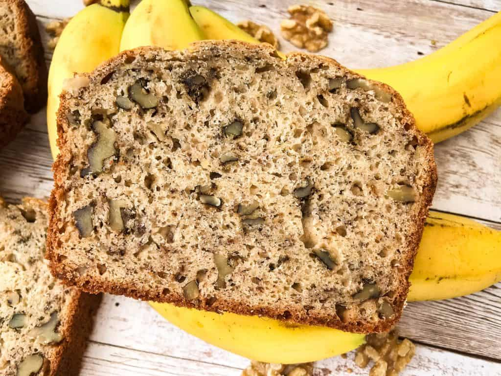 Close up of a slice of banana nut bread on top of bananas