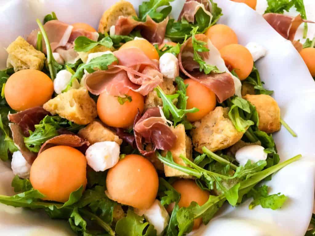 Horizontal image of Prosciutto Melon Panzanella Salad in a white bowl