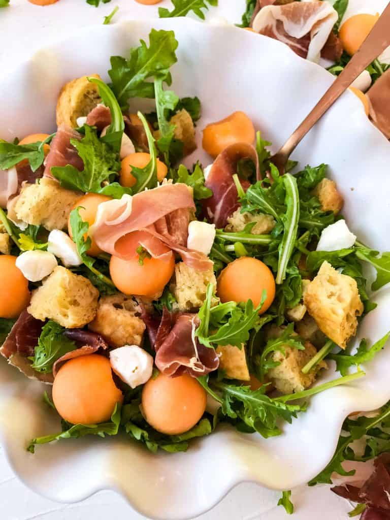 Close up of Prosciutto Melon Panzanella Salad with a spoon in it