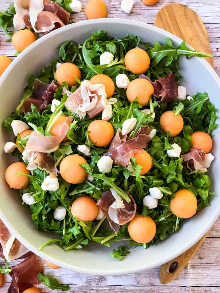 A bowl full of Prosciutto Melon Salad with Mozzarella and Arugula with a wood spoon