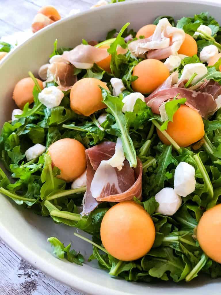 A close up of Prosciutto Melon Salad with Mozzarella and Arugula