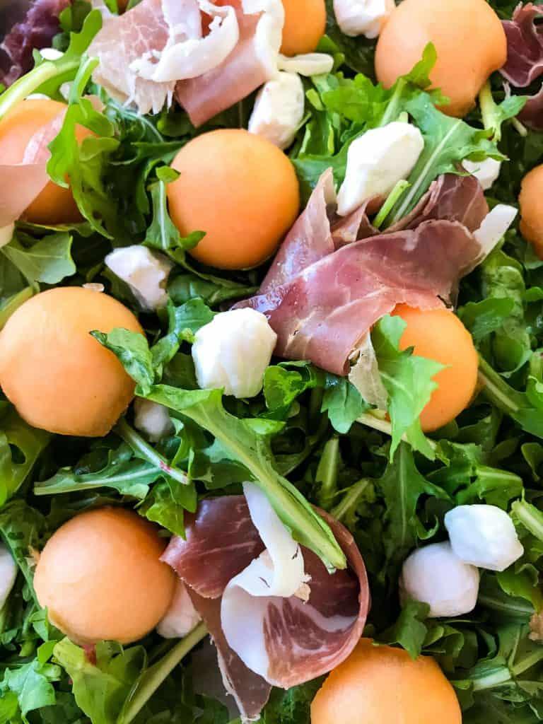 A salad filled with cantaloupe, prosciutto, and mozzarella