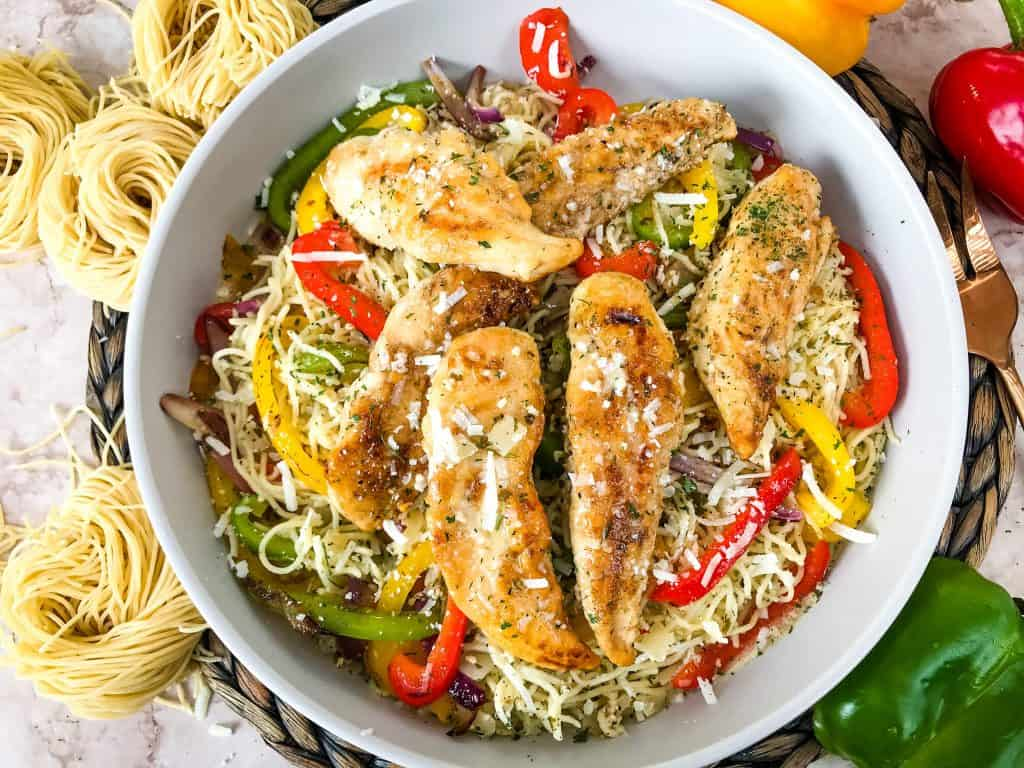 Copycat Olive Garden Chicken Scampi in a bowl surrounded by fresh pasta and peppers