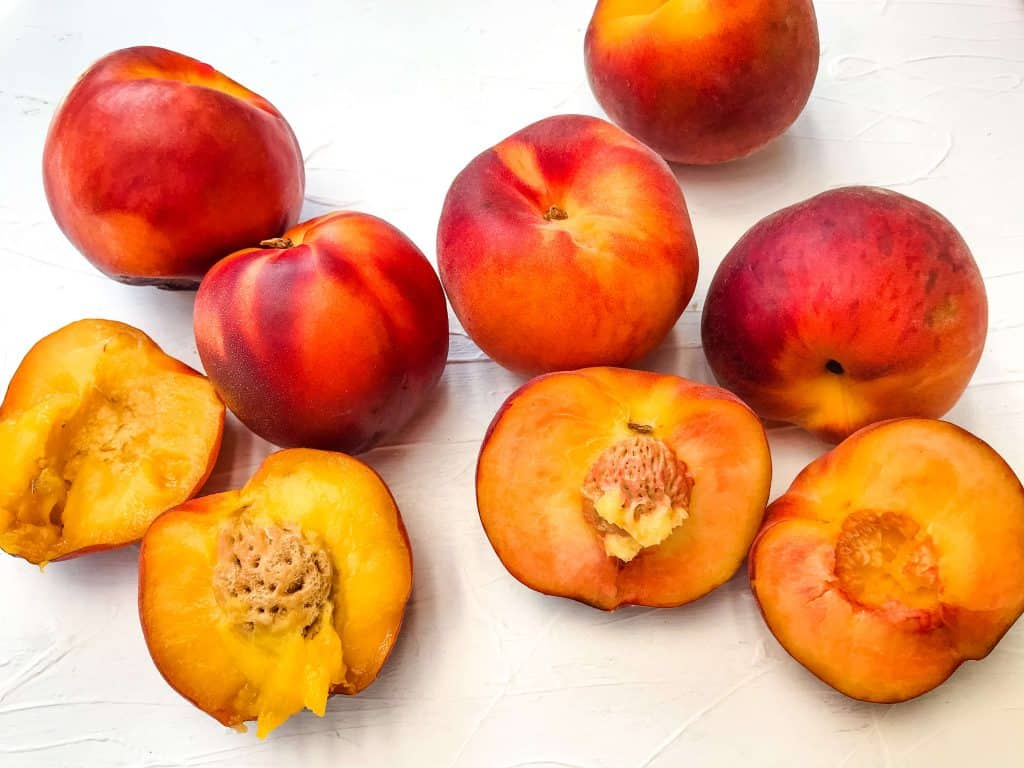 The Difference Between Peach and Nectarine side by side with cut and whole fruit on a white background