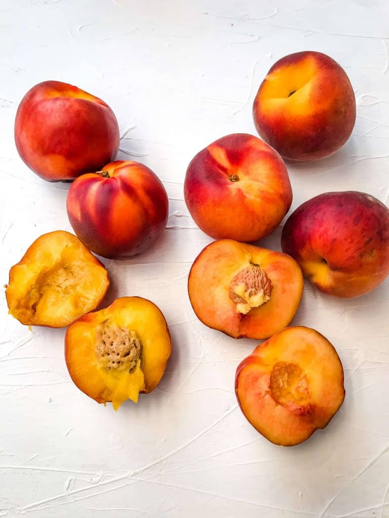 The Difference Between Peach and Nectarine with the fruit side by side on a white background