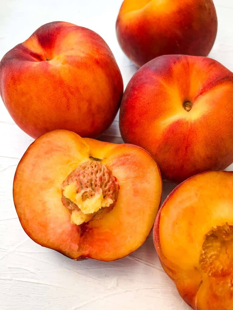 Close up of cut open peach and some whole peaches for the Difference Between Peach and Nectarine