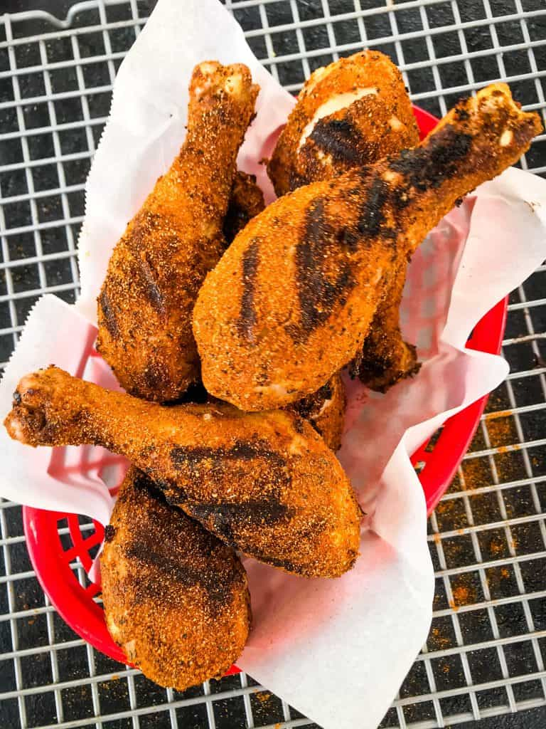 A red basket with white paper full of Dry Rub Cajun Grilled Chicken Drumsticks on a wire rack