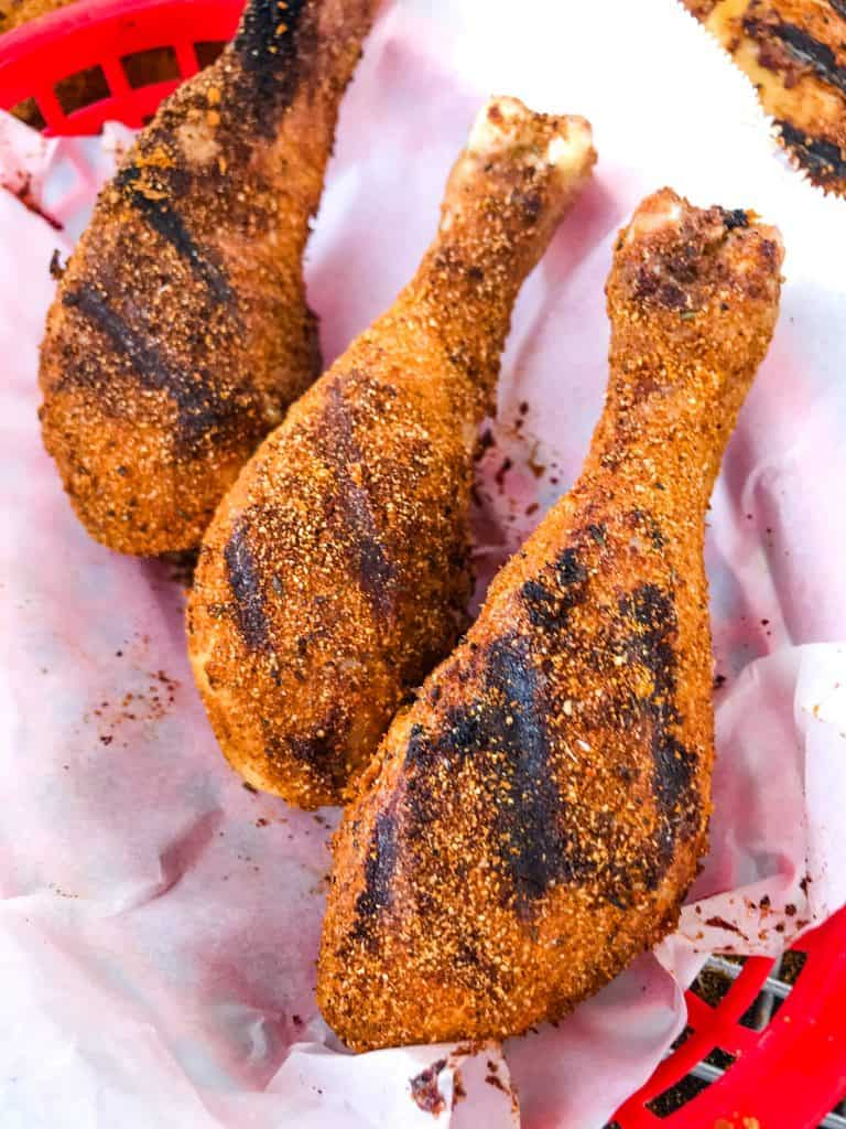 Three Dry Rub Cajun Grilled Chicken Drumsticks lined up in a red basket with white paper