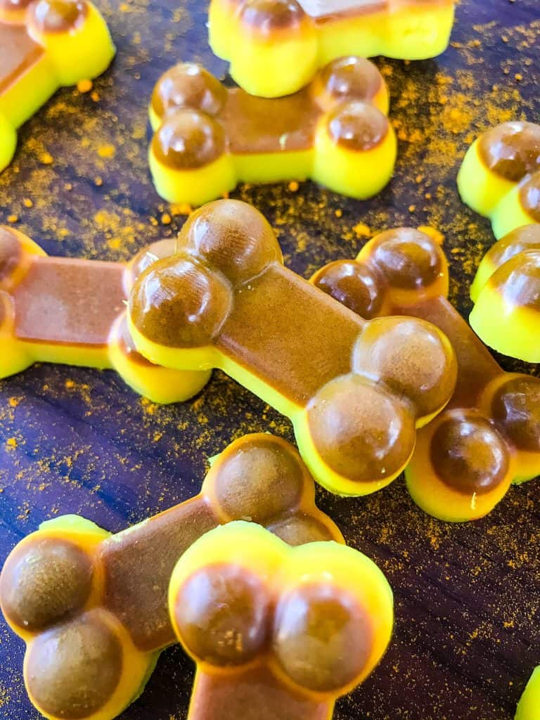 Stacked yellow and brown Frozen Turmeric Coconut Dog Treats on a black background