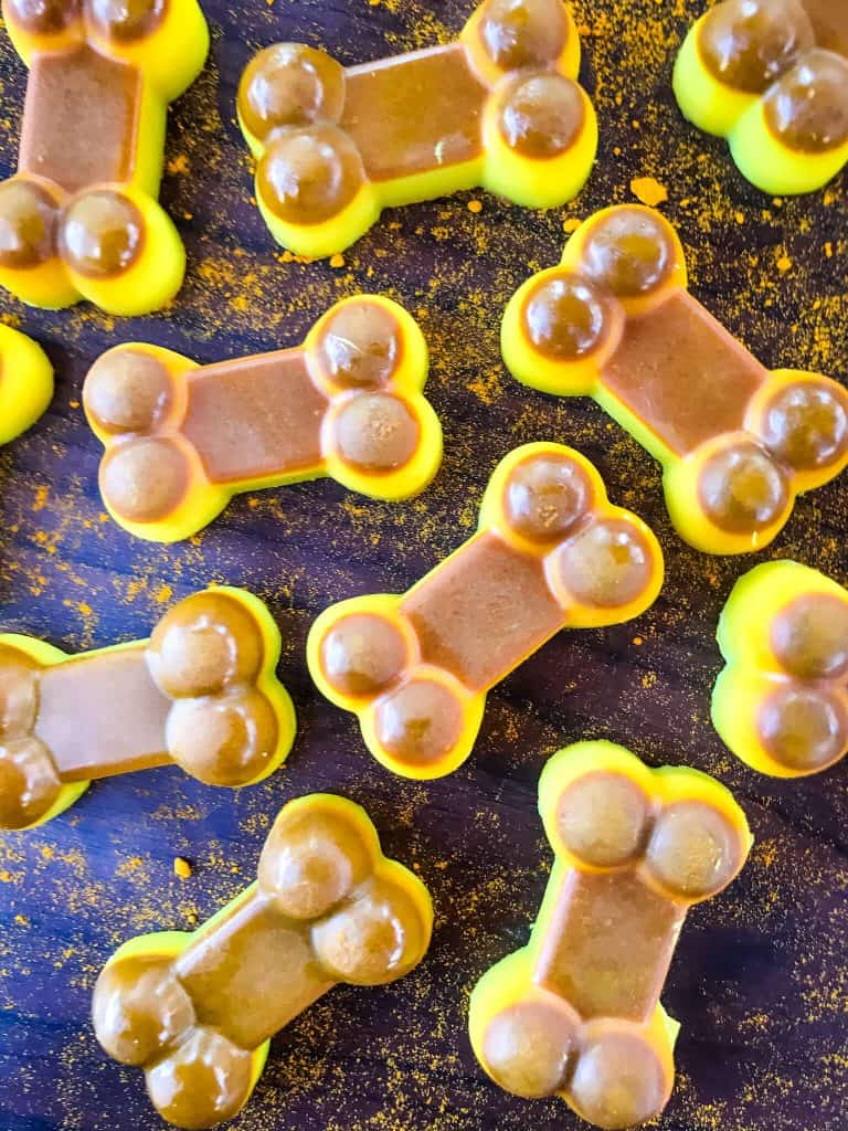 Brown and yellow Frozen Turmeric Coconut Dog Treats on a black background