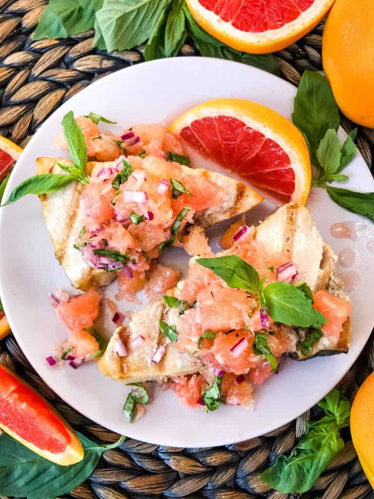 Overhead shot of two Basil Grapefruit Grilled Swordfish Steaks on a plate surrounded by grapefruit and basil