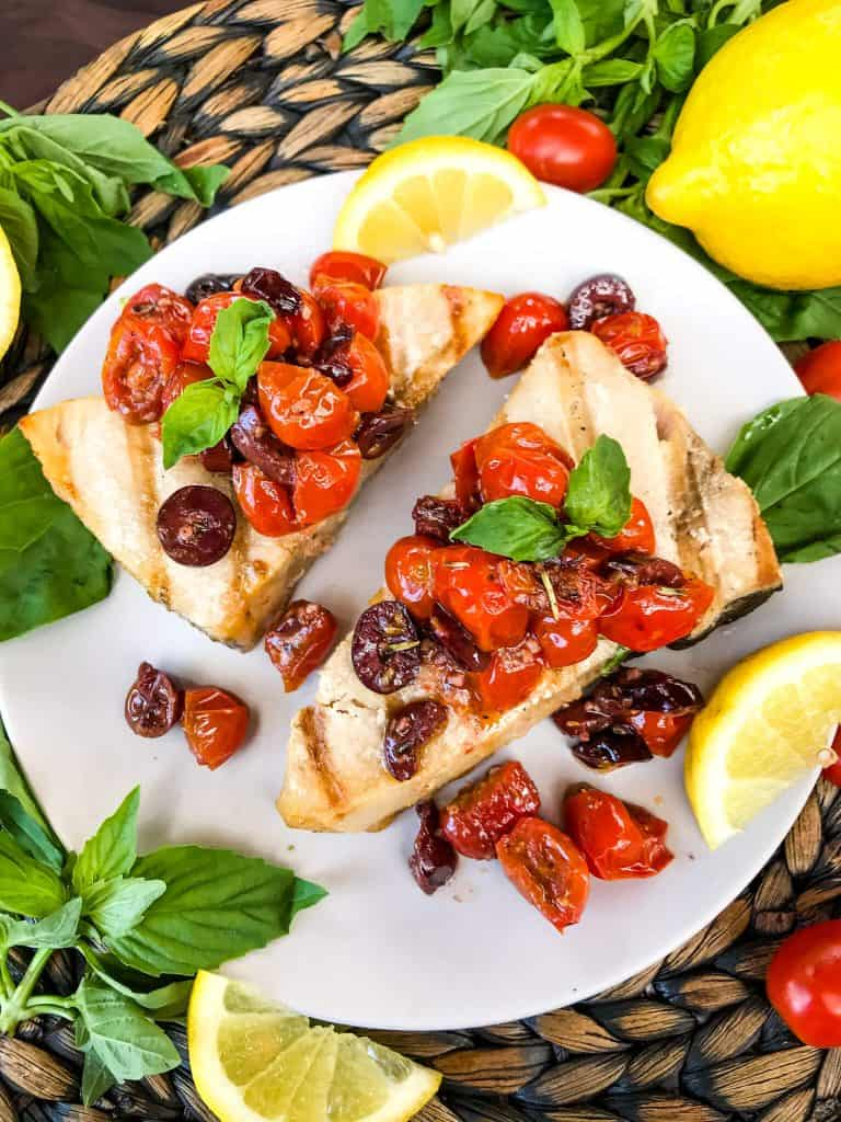 Two pieces of fish with tomato olive relish on top on a plate surrounded by lemons and basil