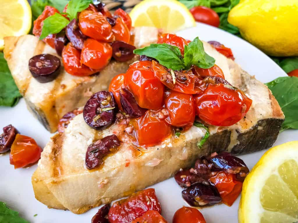 A close up of a piece of Grilled Swordfish Steaks with Tomato Olive Relish