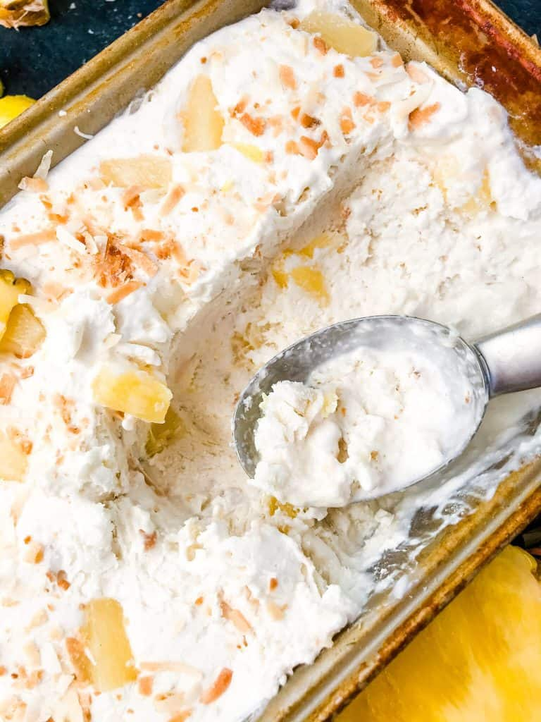 A pan full of No Churn Pina Colada Ice Cream with an ice cream scoop on top