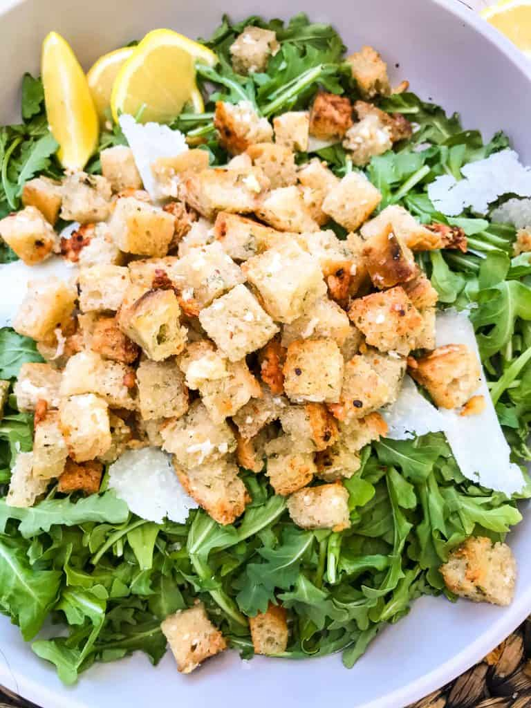 Close up of Homemade Parmesan Garlic Croutons on arugula with Parmesan shavings
