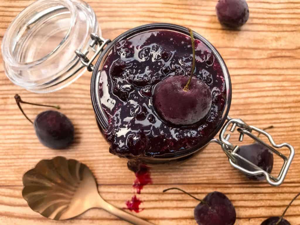 Horizontal glass jar with cherry spread