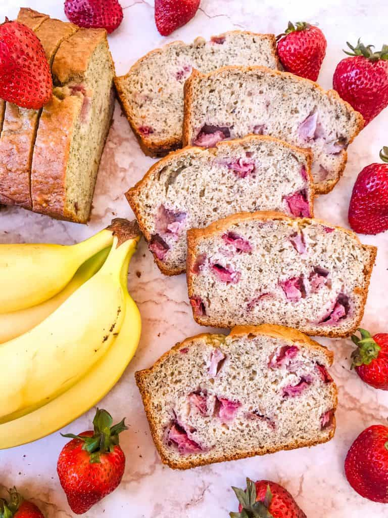 Several slices of Strawberry Banana Bread fanned out and surrounded by bananas and strawberries