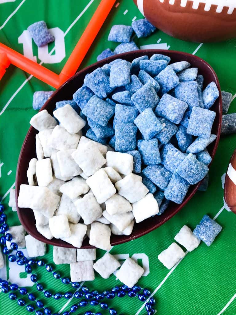 A football bowl with white puppy chow on one side and blue puppy chow on the other, on top of a green football field table cloth