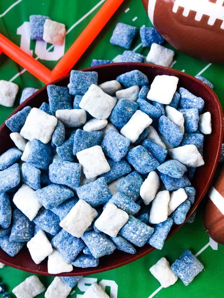 Blue and white muddy buddies mixed together in football bowl with green football field tablecloth
