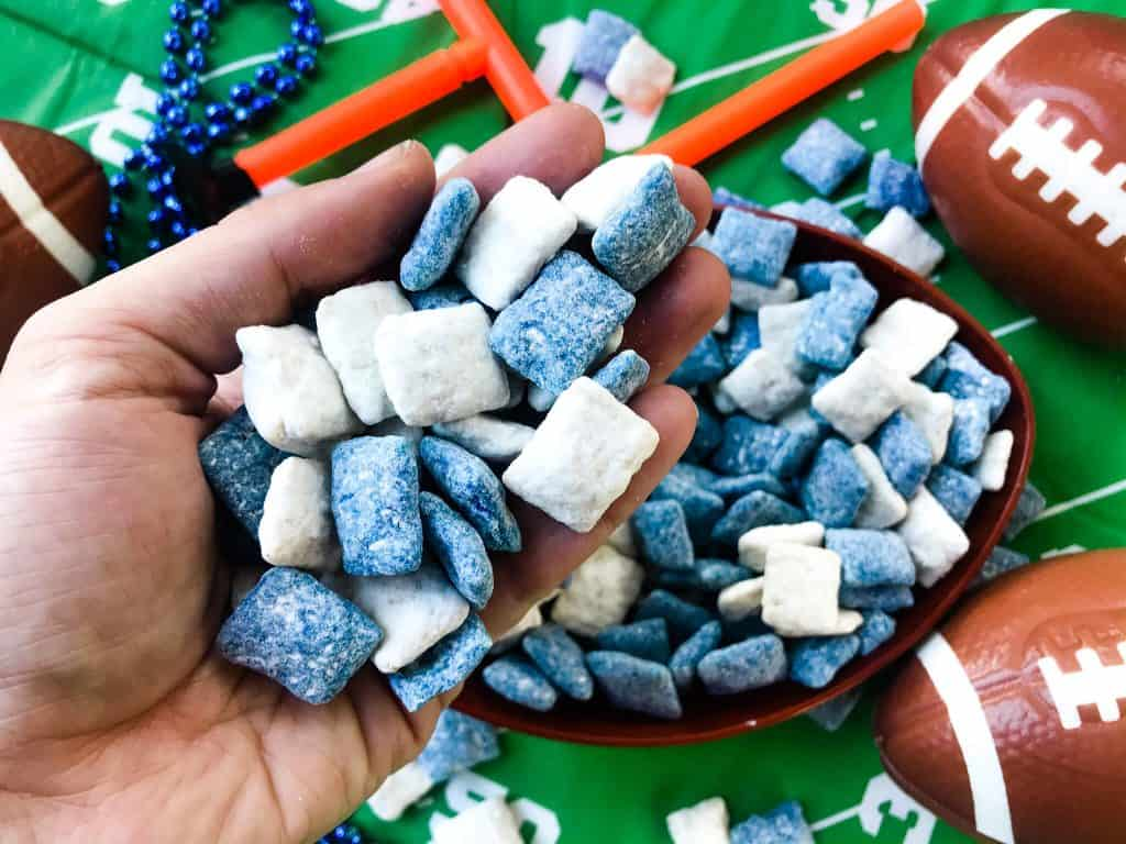 Hand holding blue and white puppy chow muddy buddies with football decor in background