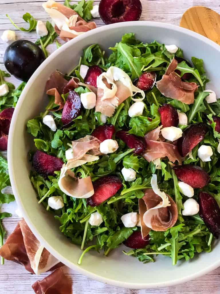 A bowl of Prosciutto Plum Arugula Salad with Mozzarella surrounded by ingredients and a wooden spoon