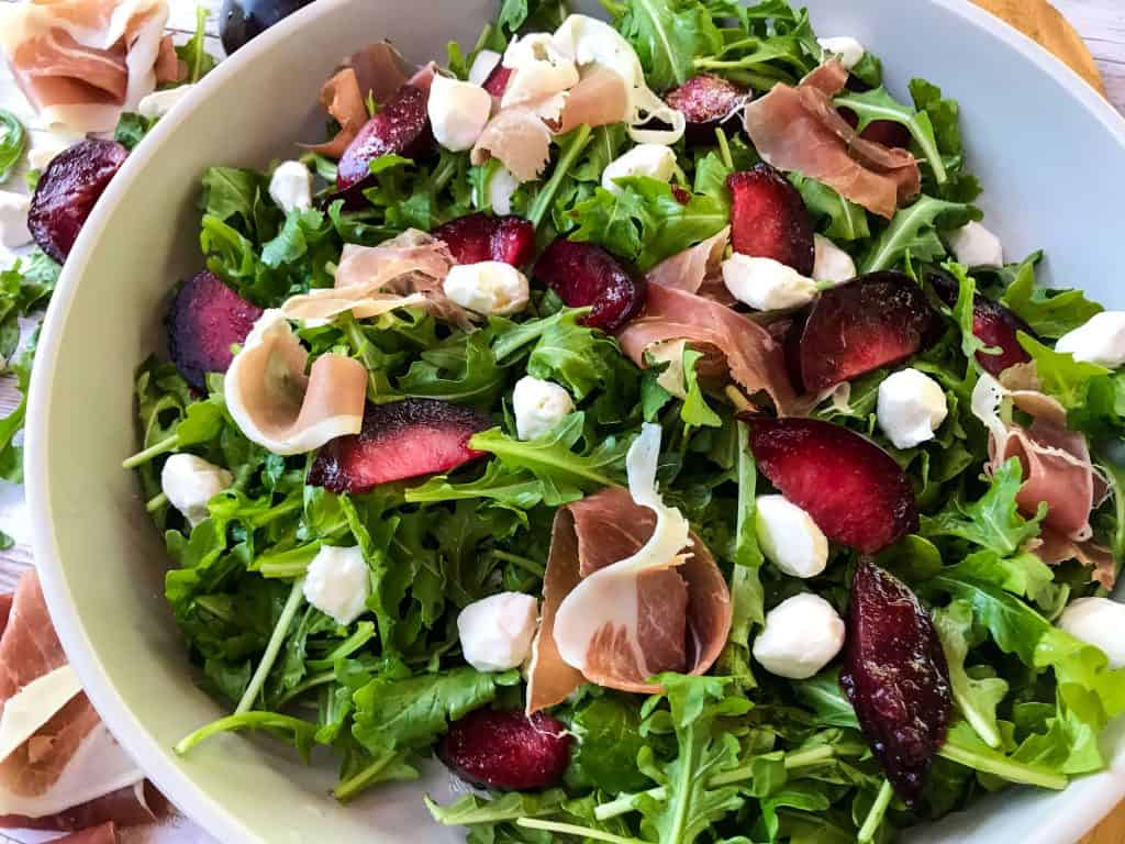 Horizontal image of Prosciutto Plum Arugula Salad with Mozzarella in a bowl