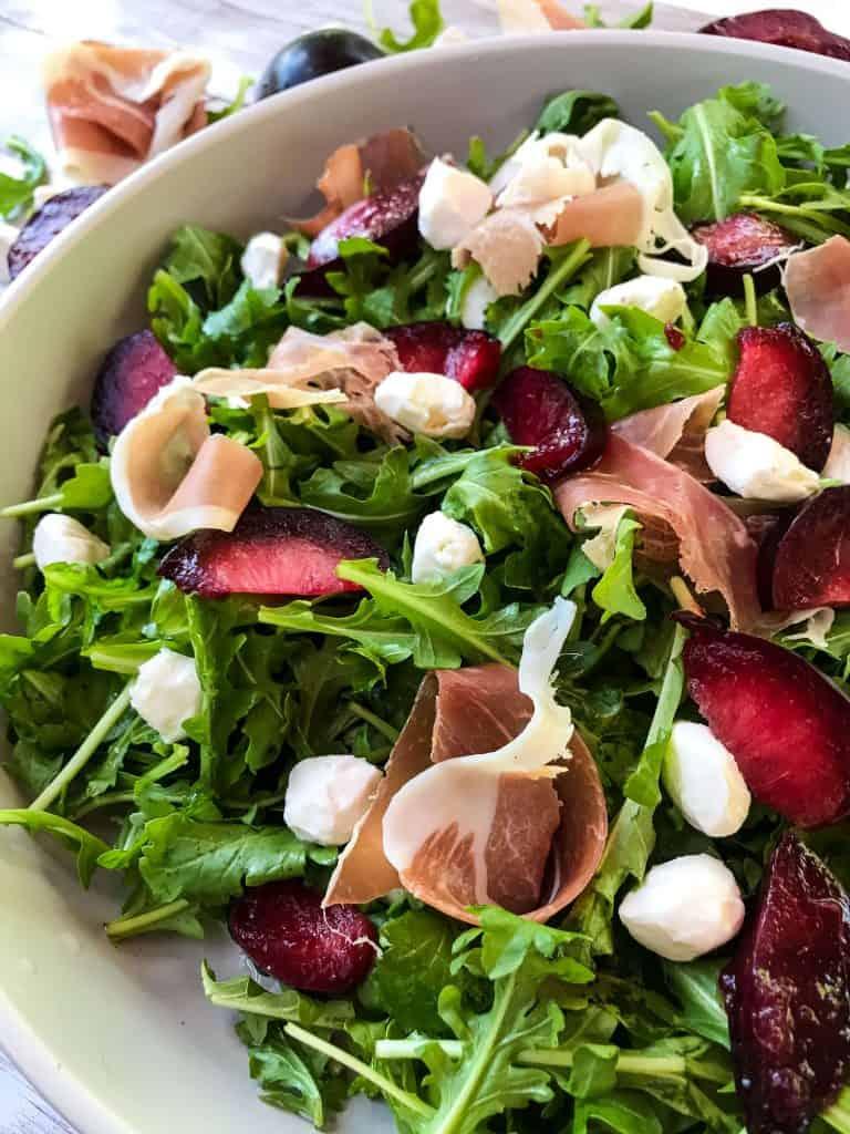Close up of Prosciutto Plum Arugula Salad with Mozzarella
